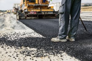 Arlington Asphalt Paving crew member working on new road construction