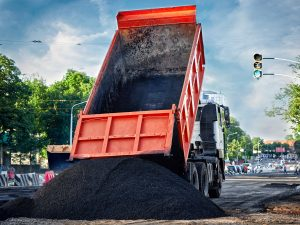 Heavy duty dump truck with long cabin unloads fresh hot smoking asphalt mix on a prepared surface for paving. Building new roadway in the city. Road construction.